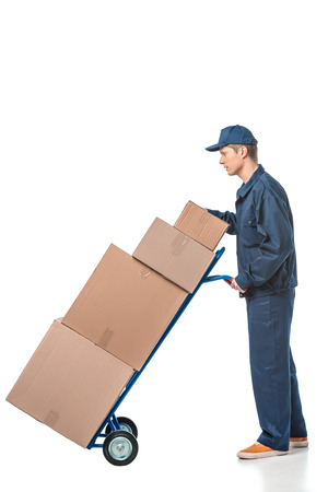 mover in uniform transporting cardboard boxes on hand truck isolated on white with copy space Foto de archivo