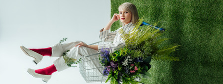 panoramic shot of fashionable girl sitting in shopping cart with fern and flowers on white with green grass