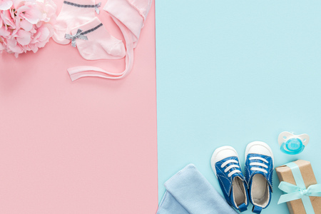 top view of pacifier, gift, hat, bonnet, sneakers, socks, bouquet on pink and blue background Reklamní fotografie