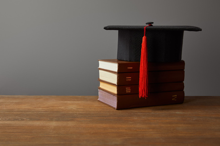 Academic cap and books on wooden surface isolated on grey