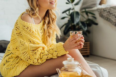 cropped view of young woman in knitted sweater sitting on bed and holding cup of tea Stock Photo