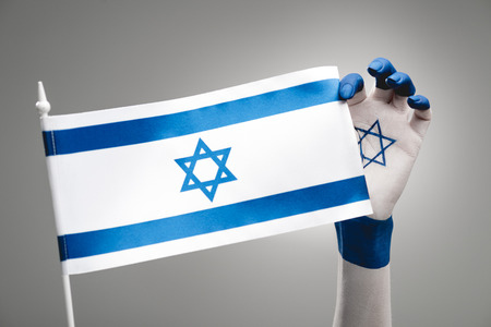 cropped view of female hand with star of david holding flag on grey