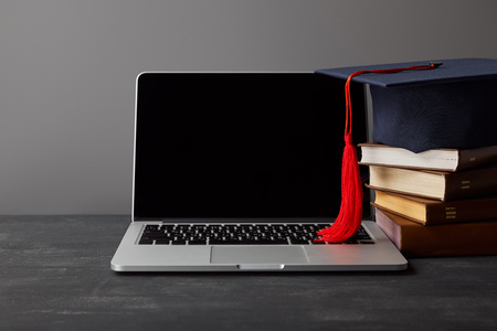 Laptop with blank screen, books and academic cap with red tassel on grey