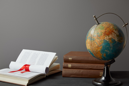Globe, books and diploma with red ribbon isolated on grey
