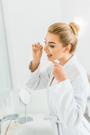 attractive and blonde woman in white bathrobe brushing teeth with dental floss
