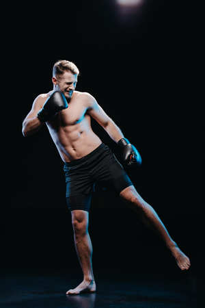 front view of muscular barefoot strenuous boxer in boxing gloves doing kick on black