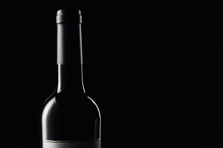 Bottle of wine with dark wrapper isolated on black 写真素材