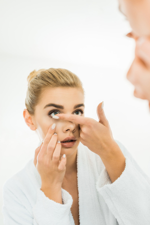selective focus of attractive and blonde woman in white bathrobe attaching contact lens Standard-Bild