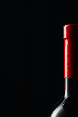 Wine bottle with red wrapper isolated on black 写真素材
