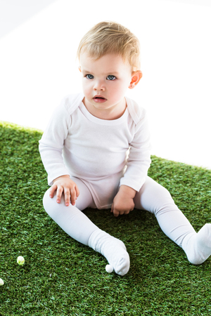 adorable blonde baby sitting on green grass isolated on white
