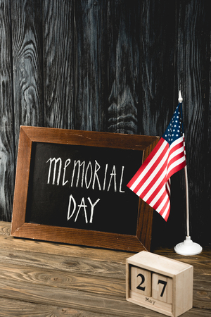 chalkboard with memorial day lettering near american flag and wooden cubes with date