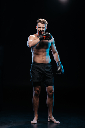 muscular barefoot sporty boxer taking off  boxing gloves with mouth on black