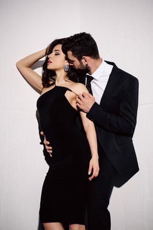 chica morena en vestido negro de pie con el hombre en blanco Foto de archivo