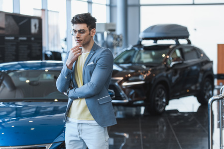 thoughtful man in glasses standing near automobiles in car showroom
