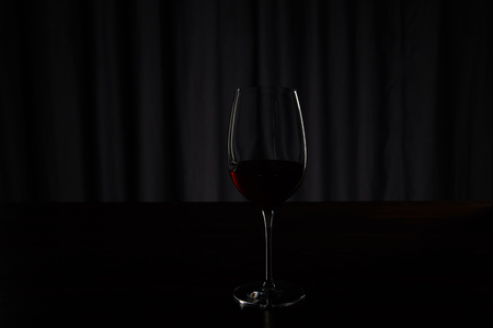 Silhouette of glass with burgundy red wine on dark Stock Photo
