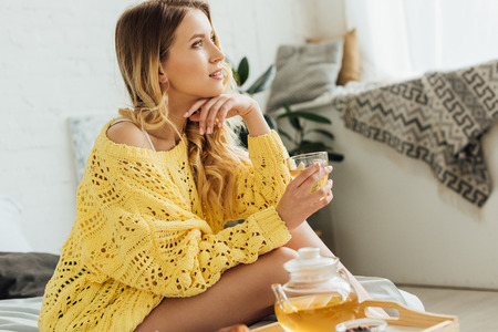 beautiful young woman in knitted sweater sitting on bed, touching face and holding cup of tea Reklamní fotografie