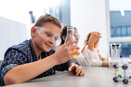 Pupils in protective goggles holding beakers during chemistry lesson