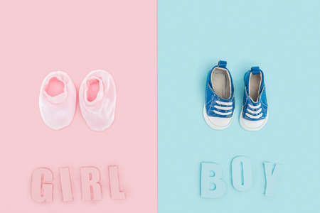 top view of boy and girl lettering and sneakers, booties on pink and blue background Banque d'images - 120172090