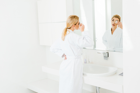 selective focus of attractive and blonde woman in white bathrobe using cotton pad and looking at mirror