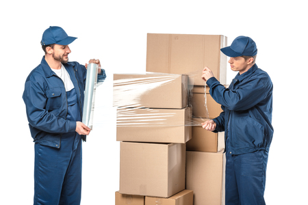 two movers wrapping cardboard boxes with roll of stretch film isolated on white