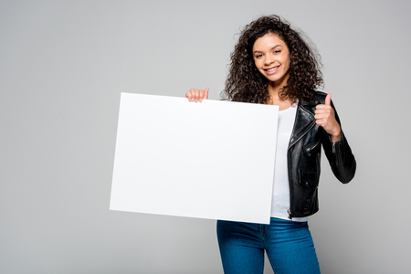 Alegre joven afroamericana mostrando el pulgar hacia arriba mientras sostiene un cartel en blanco aislado en gris