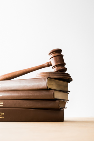 bottom view of gavel on pile of brown books on wooden table isolated on white