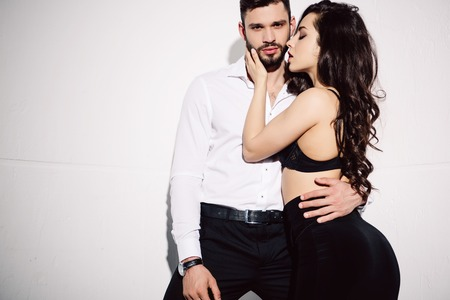 beautiful woman in black bra touching handsome bearded man on white
