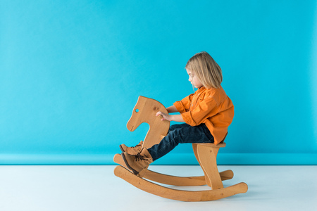 side view of blonde and cute kid riding on rocking horse on blue background Stockfoto