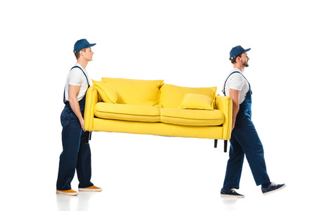 side view of two movers transporting yellow sofa on white