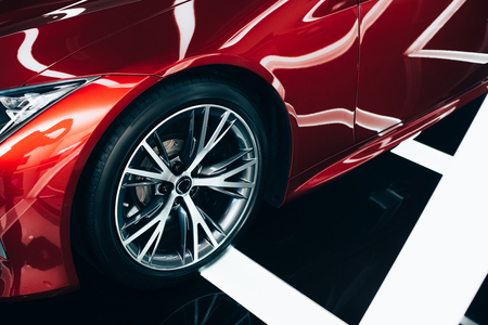 nouvelle automobile rouge brillante avec roue métallique dans la salle d'exposition de voitures