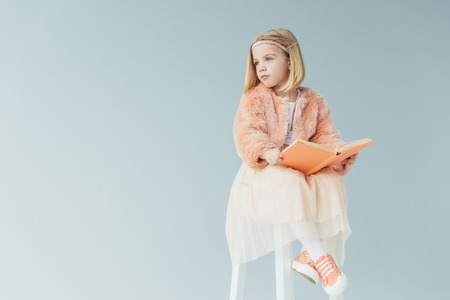 kid in faux fur coat and skirt sitting on highchair and holding book isolated on grey Stock Photo
