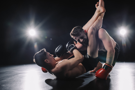 strong mma fighter in boxing gloves doing painful chokehold with legs to another sportsman on floor 스톡 콘텐츠