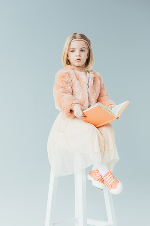 cute kid in faux fur coat and skirt sitting on highchair and holding book isolated on grey