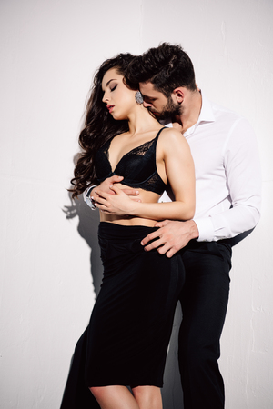 handsome man kissing neck of beautiful woman in black dress on white Stock Photo