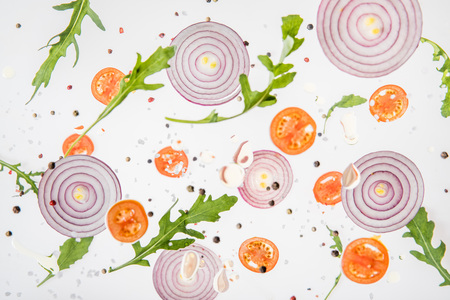 background with sliced tomatoes, red onions, garlic, arugula leaves and spices Imagens - 120173662