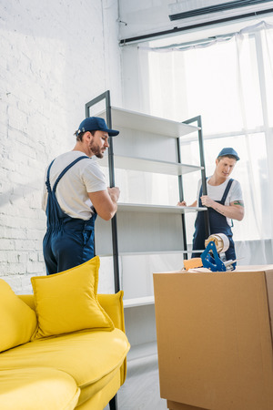two movers in uniform transporting rack in apartment