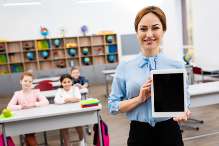 Smiling teacher in blue blouse showing digital tablet with blank screen 写真素材