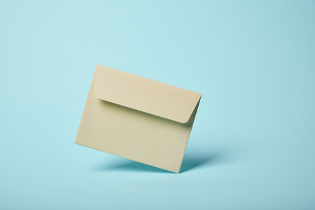 beige and blank envelope on blue background with copy space