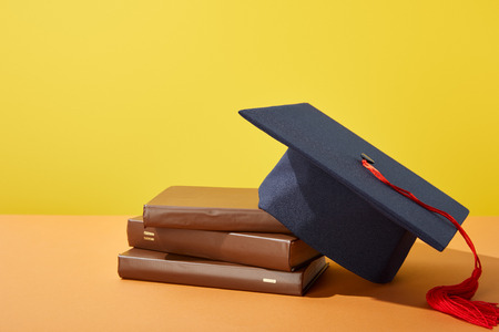 Brown books and academic cap with red tassel on orange surface isolated on yellow Standard-Bild - 120173697