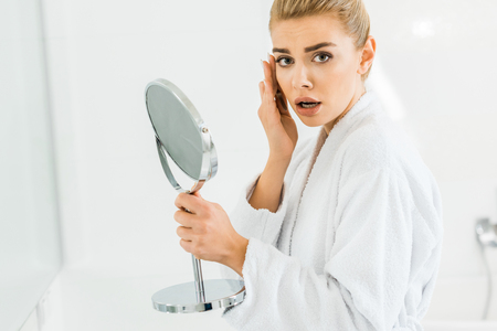 surprised and beautiful woman in white bathrobe holding mirror and looking at camera Stok Fotoğraf