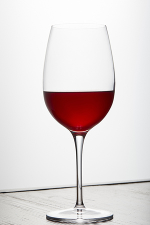 Glass of red wine on dark surface on white