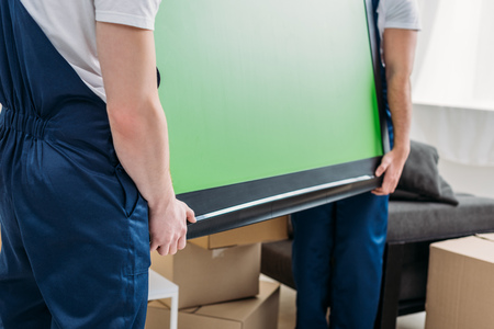 cropped view of two movers in uniform transporting tv with green screen in apartment