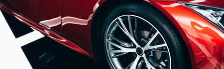 panoramic shot of new shiny red automobile with metallic wheel