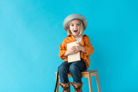 surprised kid in jeans and orange shirt sitting on stairs and holding book isolated on blue