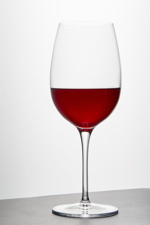 Wine glass with red wine on dark surface on white 写真素材
