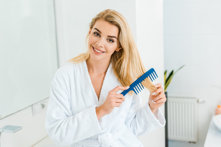 beautiful and smiling woman in white bathrobe looking at camera and using comb in bathroom