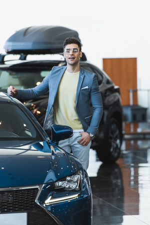 happy man in glasses standing near automobile in car showroom