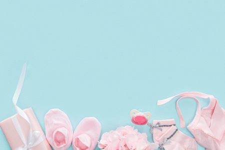 top view of pacifier, gift, booties, bonnet, socks and bouquet on blue background