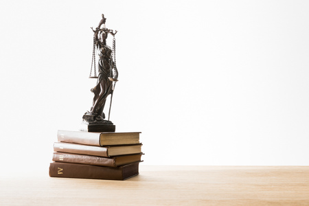 bronze figurine with scales of justice on brown books on wooden table isolated on white