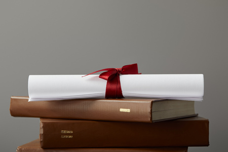 Brown books and diploma with red ribbon isolated on grey